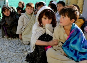 Afghan children wait to receive basic medical care and clothing on Camp Clark, Khowst province, Afghanistan, Dec. 22.